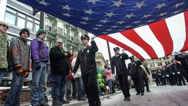 Second Lt. Jason Stupski, from the Vestal Fire Department, carries an American flag with others as they walk down Court Street on Saturday during the 47th annual St. Patrick's Day Parade in downtown Binghamton.