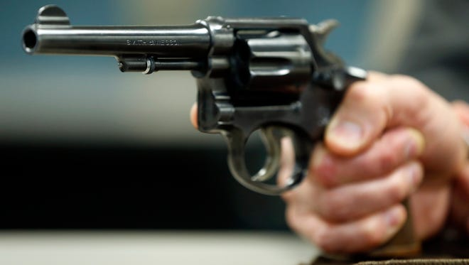 In this March 25, 2015, photo, Internal Revenue Service agent Jonathan Larsen, holds a Smith & Wesson .38 Special during an interview in Mountainside, N.J. The gun belonged to IRS investigator Michael Malone, the man who went undercover to infiltrate Al Capone's gang in the 1930s and eventually brought down the feared mobster.