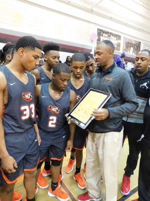 Opelousas boys' basketball coach Lorenso Williams explains a defensive scheme on Tuesday night during his team's 86-41 win over Eunice High in the Northwest Holiday Basketball Tournament first round contest.