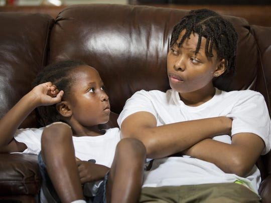 Vincent Samuel DuBose, then 4, and his sister, Teaila Williamston, then 15, listen to DaShonda Reid talk about their father, Sam DuBose, during an interview in August 2015 -- just weeks after a white police officer shot and killed the unarmed DuBose in a Mount Auburn traffic stop.