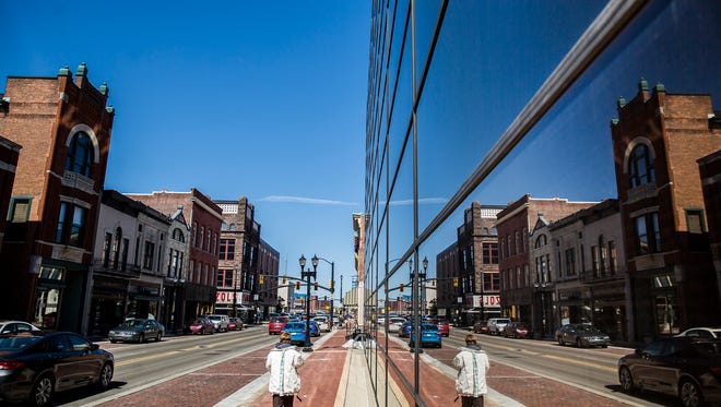 Downtown Muncie reflected in the windows of a former bank building on Walnut Street.