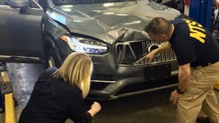 NTSB investigators examine a self-driving Uber vehicle.