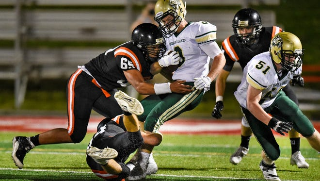St. Cloud Tech players team up to tackle Matt Mohr of Chisago Lakes during the third quarter of the Friday, Sept. 2, game at Husky Stadium in St. Cloud.