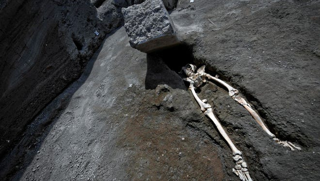 The legs of a skeleton emerge from the ground beneath a large rock believed to have crushed the victim's bust during the eruption of Mt. Vesuvius in A.D. 79, which destroyed the ancient town of Pompeii, at Pompeii's archeological site, near Naples, on May 29. The skeleton was found during recent excavations and is believed to be of a 35-year-old man with a limp who was hit by a pyroclastic cloud during the eruption.