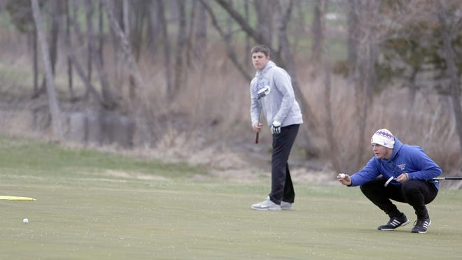Boonville senior Brayden Page watches the ball after hitting a long putt during a match his sophomore year at Hail Ridge Golf Course in Boonville.  Teammate Mason Hage (far right) lines his ball up for a putt on the same hole.