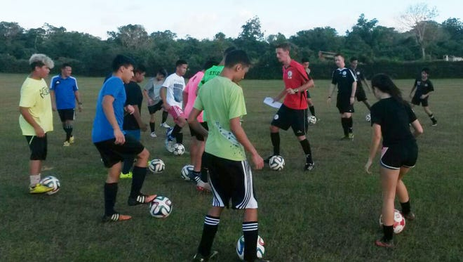 Gary White, Guam Football Association Technical Director (in black), and Matao midfielder Jan-Willem Staman (in red), engages in a training session with youth soccer players from the ASC Trust Islanders in Harmon. The GFA technical department recently launched its Club + Player Development Program, which features GFA licensed coaches to assist youth soccer clubs with training sessions. Photo courtesy of GFA Executive Committee member Kun Ho Rhee.