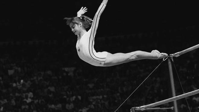 """Nadia Comaneci, of Romania, dismounts from the uneven parallel bars during a perfect """"10"""" performance at the Summer Olympic Games in Montreal, Canada, July 18, 1976."""