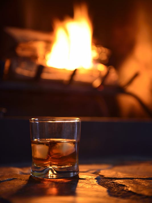 glass of hard liquor with ice cubes and fireplace