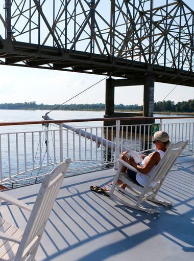 Cathy Fowler, from Blythe, Ga., reads on the sun deck of the American Queen as it passes under the Interstate 155 bridge while the boat makes it's way down river from New Madrid, Mo. to Memphis.