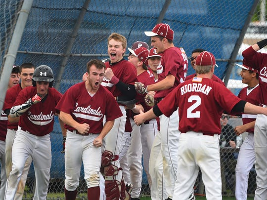 Pompton Lakes pitcher, Christian Ferrara (no. 13, not shown) who hit three run homers to lead the game in the beginning of the sixth inning, is congratulated by his teammates at home as they play against Passaic Tech for the Passaic County baseball tournament championship game at Passaic Tech's field in Wayne on May 16th, 2017. Pompton Lakes defeated Passaic Tech 10 to 6 and won the championship.