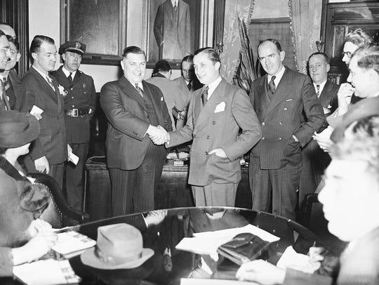 Governor Harold G. Hoffman, left, shown shaking hands