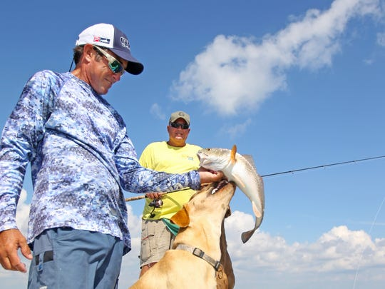 Capt. Scott McCune with his trademark canine deckhands, Trigger and Kona.