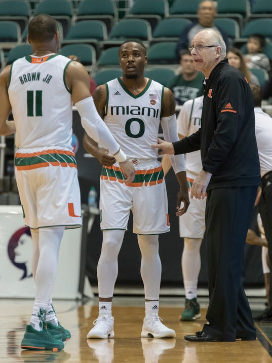 Miami coach Jim Larranaga, right, talks with guards Bruce Brown Jr. (11) and Ja'Quan Newton (0) during the second half of an NCAA college basketball game against New Mexico State at the Diamond Head Classic tournament, Saturday, Dec. 23, 2017, in Honolulu. New Mexico State won 63-54. (AP Photo/Eugene Tanner)