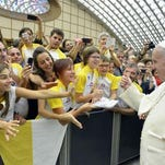 Pope Francis gives a thumbs-up to a group of young people during his weekly audience in Paul VI hall at the Vatican.