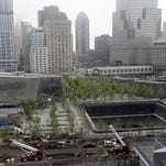 The pavilion entrance to the National September 11 Memorial Museum, left, is next to one of the memorial reflecting pools, right, at the World Trade Center, Thursday, May 15, 2014 in New York.