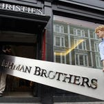 The Lehman Brothers corporate sign in polished metal is taken into an auction house in London on Sept. 24, 2010.