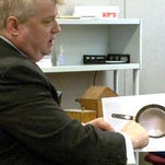 Patrick Allen's defense attorney John Allen holds a photograph of the frying pan that was alledgedly used in the murder of Kimberly Allen.
