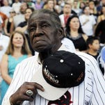 In a Aug. 24, 2013, file photo, former Negro Leaguer and Chicago White Sox player Minnie Minoso stands during the national anthem.