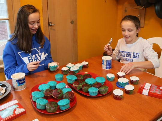 Madeline Kogler (right) has enjoyed learning about Hanukkah from her friend, Rachel Abramson. Here the friends, both 13, decorate cupcakes — some for Christmas and others for Hanuukah.