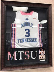 "A jersey of Abbey Sissom hangs in the lobby of First National Bank's Woodbury branch. ""I think it helps say, 'Thank you, Abbey, for what you've done for this community,'"" bank president Tim Spry said."