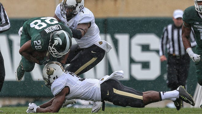 Michigan State Spartans running back Madre London (28) is upended by Purdue Boilermakers linebacker Danny Ezechukwu (36) during the 1st half of a game at Spartan Stadium.