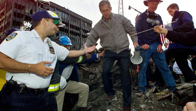 """In this Friday, Sept. 14, 2001 file photo, Joseph Esposito, left, chief of department of the New York Police Department, offers help as President George W. Bush steps off of a pile of rubble after speaking at ground zero of the World Trade Center site in New York. Esposito, then the NYPD's top uniformed officer, was struck by """"the camaraderie, the unity"""" of those days."""