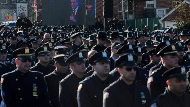 This Dec. 27, 2014, file photo shows police officers turning their backs as New York City Mayor Bill de Blasio speaks at the funeral of New York city police officer Rafael Ramos in the Glendale section of Queens, in New York. Mayor Bill de Blasio is winding down his first year in office, which saw success at fulfilling many of his liberal campaign promises. But the year ends with his young mayoralty facing its biggest crisis yet: an open rebellion from police officers who don't believe the mayor supports them.