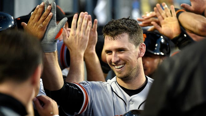 Jun 19, 2015; Los Angeles, CA, USA;  San Francisco Giants catcher Buster Posey (28) is congratulated in the dugout after hitting a grand slam home run against the Los Angeles Dodgers during the third inning at Dodger Stadium. Mandatory Credit: Richard Mackson-USA TODAY Sports