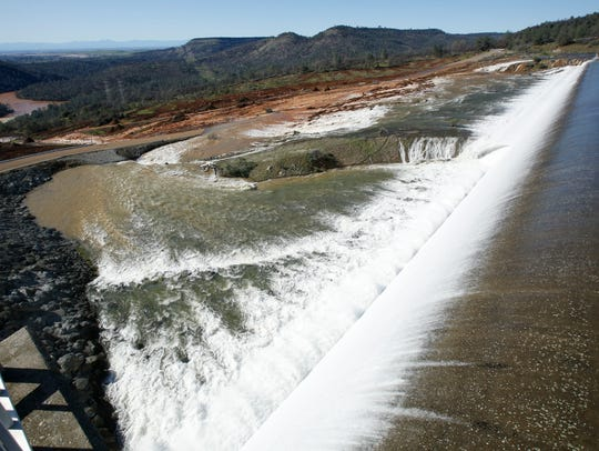 Water flows over the emergency spillway at Oroville