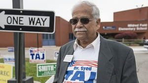 Dr. Syed Taj waits for voters to arrive Tuesday at a polling place in Canton.