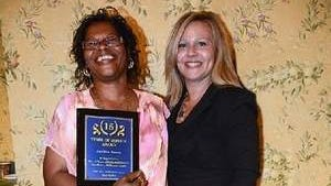 Addline Sanon shows off her plaque, presented to her by Dawn Shourt, Executive Director, The Chelsea at Tinton Falls