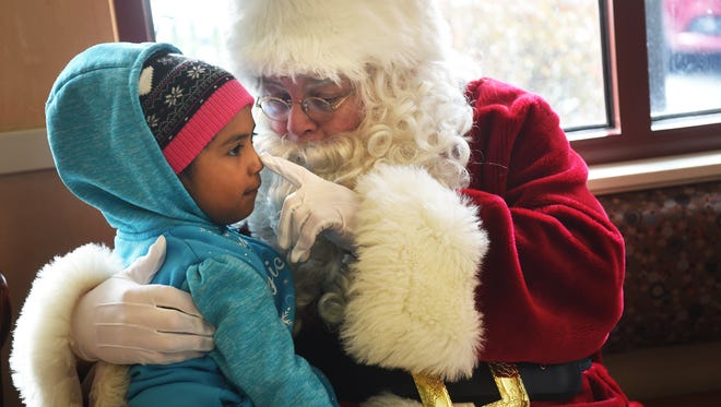 Reno local Bob Gailor plays Santa Claus and interacts with Jadalynn Rios as she goes for breakfast with her family to the International House of Pancakes in Spanish Springs on Dec. 23, 2016. Gailor has been donning the Santa suit for the past 50 years, and his father did the same for 66 holiday seasons.