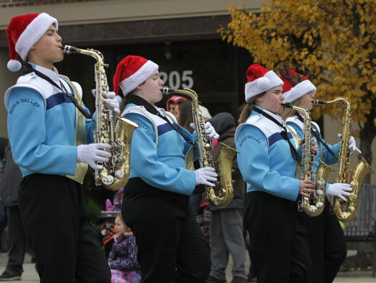 The River Valley marching band struts down center Street