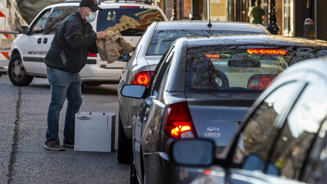 Mark Forinash, the owner of Cafe Moxo, works a line of cars along East Adams Street, that stretched out down Fifth Street, as he hands out bagged meals to anyone in need, Sunday, Nov. 15, 2020, in Springfield, Ill. Forinash, along with his wife Shawna, and general manager Brandon Hughes gave out 500 meals in 20 minutes.