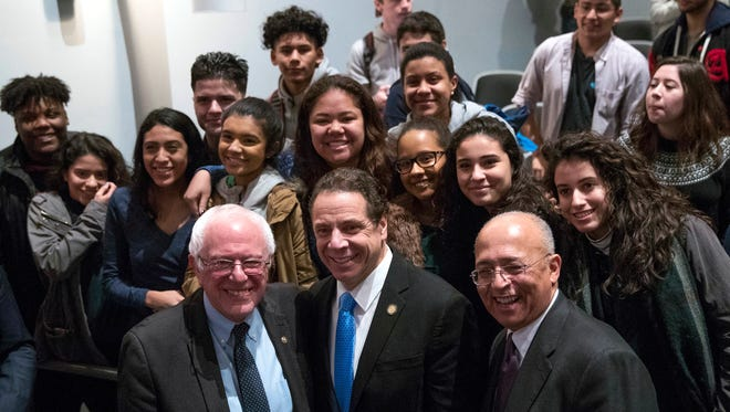 Sen. Bernie Sanders, I-Vt., left; New York Gov. Andrew Cuomo, a Democrat; and and the chairman of the Board of Trustees of The City University of New York, William C. Thompson, pose Jan. 3, 2017, with students at LaGuardia Community College in New York.