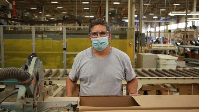 Un empleado de Haworth, con sede en los Países Bajos, usa una máscara en el trabajo a principios de 2020. Haworth, uno de los empleadores más grandes de la región, ofrece incentivos únicos para atraer y retener a los trabajadores.