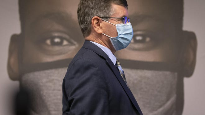 """Springfield Mayor Jim Langfelder walks past one of the images used by Illinois Governor JB Pritzker to unveil a new mask awareness campaign called """"It Only Works If You Wear It"""" during a press conference at the IEMA State Emergency Operations Center, Monday, August 3, 2020, in Springfield, Ill. The new $5 million awareness campaign will encourage Illinois residents to wear a face covering every time theyÕre in public and will be advertised on broadcast and cable television, radio, billboards and social media to the communities with the greatest risk from COVID-19."""