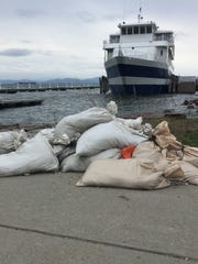 "Sandbags are stacked as a precaution against flooding Wednesday at the ECHO Center sidewalk in Burlington. The ""Spirit of Ethan Allen"" excursion ship rocks in wind-blown waves. Photographed April 19, 2017."