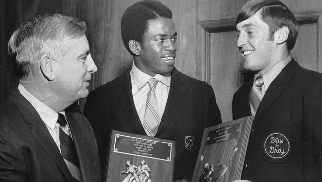 Memphis State's Billy Murphy (left), Gerald Tinker (center) and David Berrong discuss hardware the two Memphis State University athletes had collected in December 1969. Tinker holds a plaque proclaiming his world indoor record in the 50 yard dash at 5.1 seconds, presented by the Florida Athletic Club, while Berrong holds a plaque for being the most outstanding player in the Blue-Gray Classic football game on Dec. 27, 1969.
