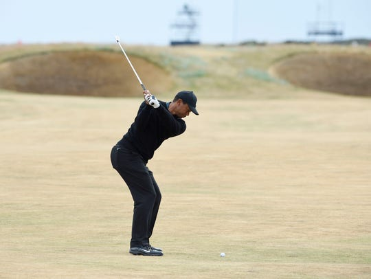 Tiger Woods plays his second shot over the spectacle