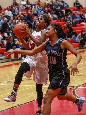 Greenville's Savannah Hughes (12) goes up for two as Christ Church's Jordan Haywood (10) defends during the Red Raiders' 51-36 win over the Cavaliers Monday night in the championship game of the Lady Raiders Thanksgiving Invitational. PAMELA DUNLAP