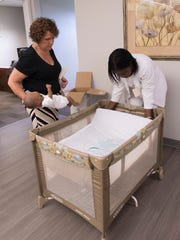 Nurse Deaun Spraglin, right, demonstrates the proper way to make a bed to promote healthy sleeping habits for infants as Theresa Chmiel, executive director of the Escambia County Healthy Start Coalition, looks on. The Healthy Start Coalition has started a public awareness campaign to remind parents about the dangers of co-sleeping with infants.