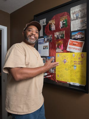 Renwick Avant shows the shadowbox filled with photos and keepsakes from his kidney transplant that is on display in his home in Pensacola on Thursday, August 31, 2017.   Avant was the first patient to receive a kidney transplant in Pensacola at Sacred Heart Hospital.
