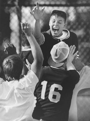 Matt Newton leaps high above his joyous teammates during action in the 1988 playoff run to the state championship for Birmingham Seahlom, dubbed the Miracle Maples by Birmingham Eccentric sports editor Marty Budner.