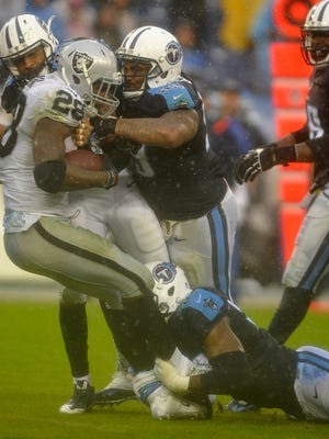 The Titans push back Raiders running back Latavius Murray during the fourth quarter.