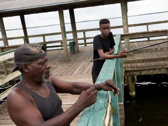 Davis Esco, of Immokalee, helps bait a hook for his