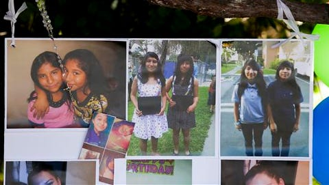 Photographs of twin sisters Lexia, left, and Lexandra Perez are displayed at a makeshift memorial near where they and Andrea Gonzales were killed in a hit and run on Halloween, Monday in Santa Ana, Calif.