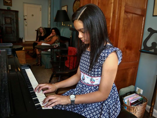 Anmy Paulino Collado plays the piano as her music teacher,