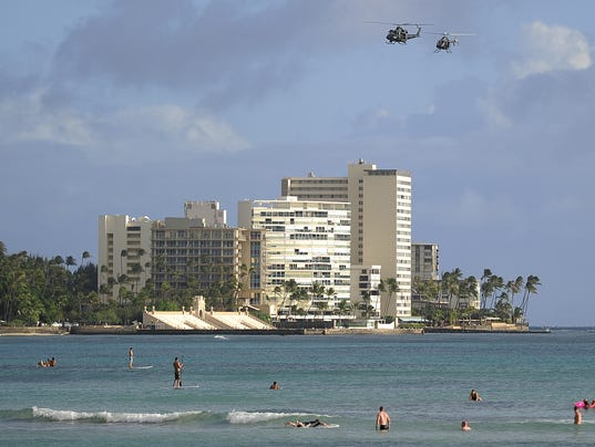 Helicopters patrol over Waikiki beach as