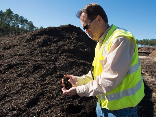 Donald Palmer, director of water reclamation for the Emerald Coast Utilities Authority, looks over organization's new compost product near the end of the manufacturing process. Under a new program, ECUA will combine yard waste materials with organic compounds from the water treatment facility to create the new compost product.